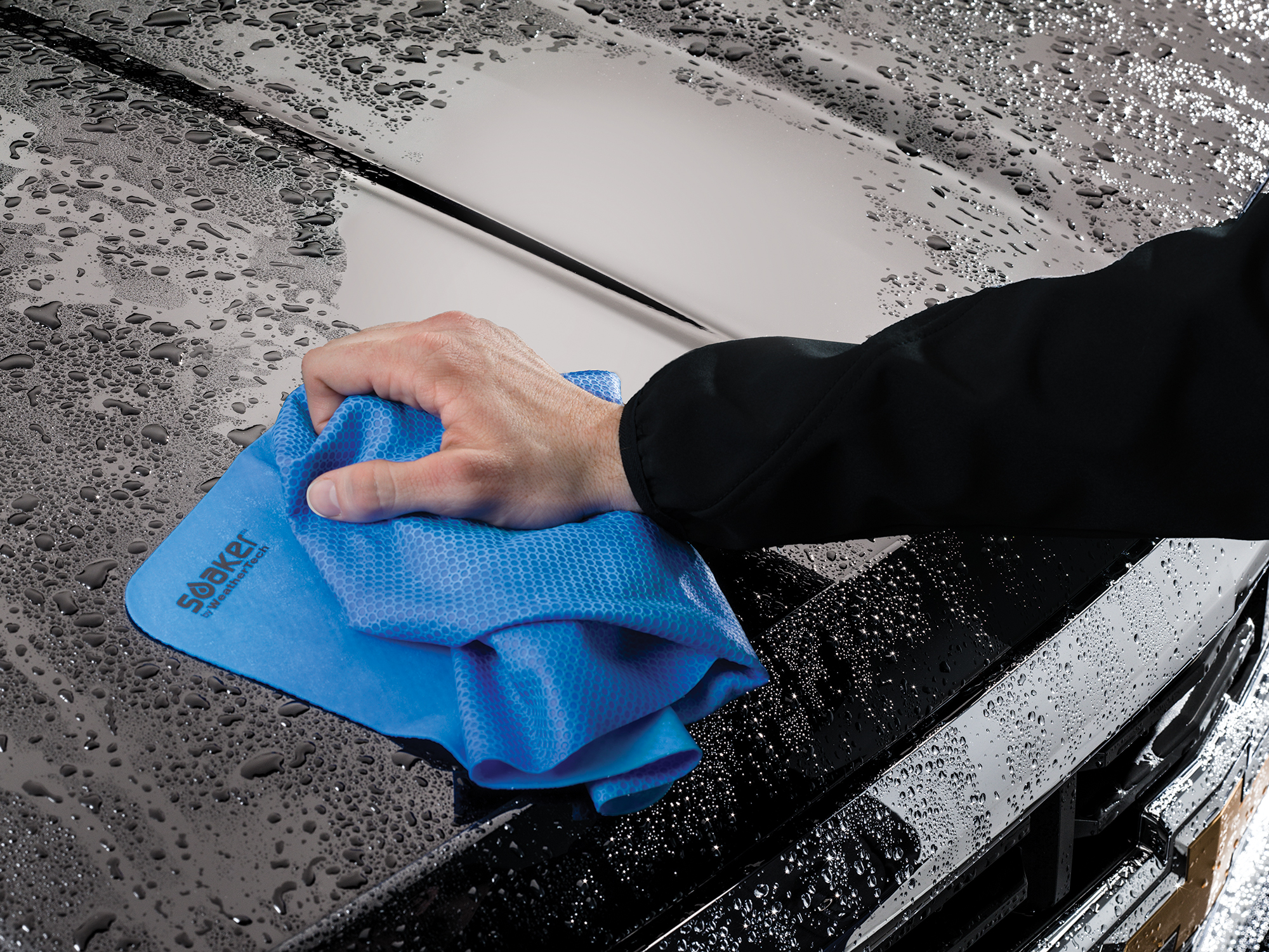 Man wiping hood of a truck with the WeatherTech Soaker.