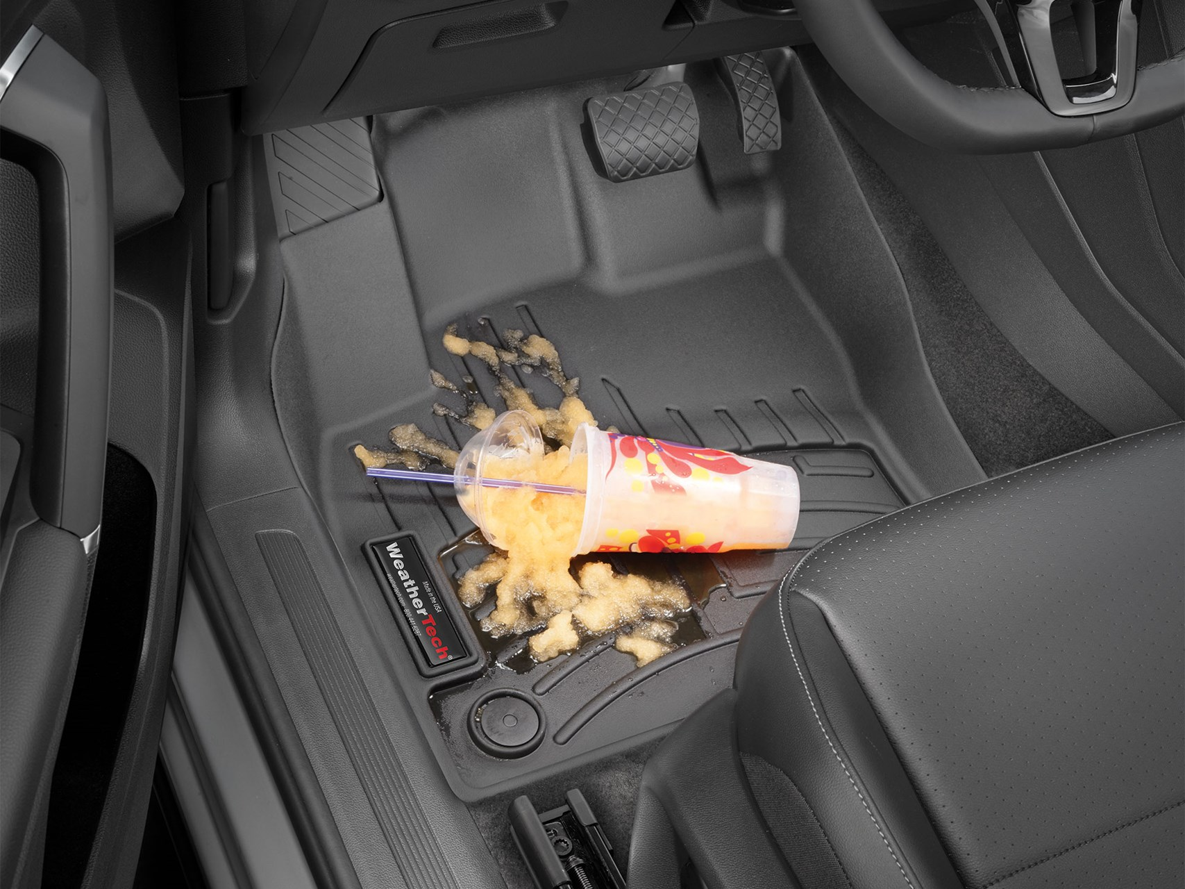 Protect your floors from spills. Image of a spilled frozen drink on a well-fitted liner on the floor of the driver's side