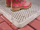wet pink rain boots on a OutdoorMat BY WEATHERTECH