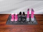 three pairs of winter boots on a black Boot Tray BY WEATHERTECH