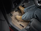 Person with muddy boots on a FloorLiner. BY WEATHERTECH
