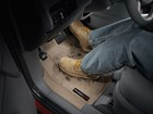 Men's muddy boots on a tan FloorLiner.  BY WEATHERTECH