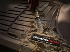 Mud being washed off a tan FloorLiner. BY WEATHERTECH