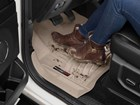 Muddy brown women's boots on a FloorLiner. BY WEATHERTECH