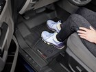 Athletic shoes on black driver's side FloorLiner. BY WEATHERTECH