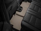 Tan second row FloorLiner against a black interior BY WEATHERTECH