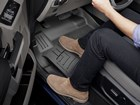 Manwith suede shoes resting feet on FloorLiner HP. BY WEATHERTECH