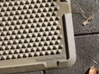 close up of a wet tan OutdoorMat outside BY WEATHERTECH