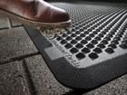 brown muddy shoe stepping on an OutdoorMat BY WEATHERTECH