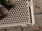muddy shoes sitting on a tan OutdoorMat BY WEATHERTECH
