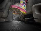 Muddy children's boot on second row FloorLiner. BY WEATHERTECH