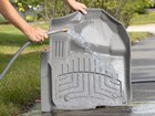 Woman rinsing off FloorLiner HP. BY WEATHERTECH