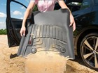 Woman pouring sand out of black FloorLiner.  BY WEATHERTECH