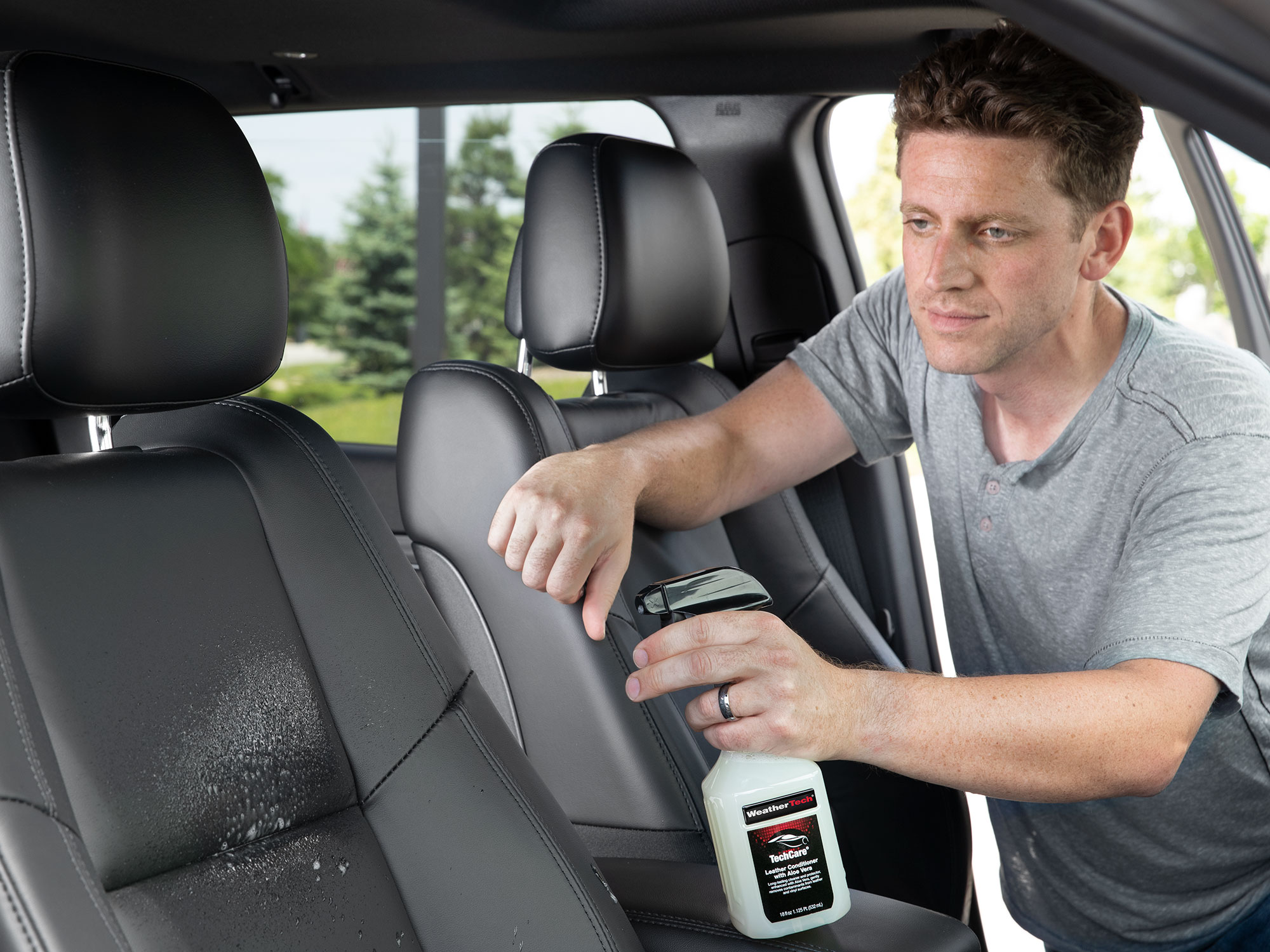 Man Spraying leather conditioner on the passenger seat.