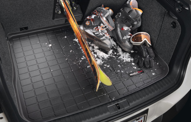 Black WeatherTech CargoLiner with skis, ski boots, ski mask, gloves and snow that is beginning to melt on top.