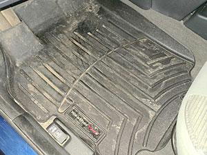 view of driver side black floorliners in car