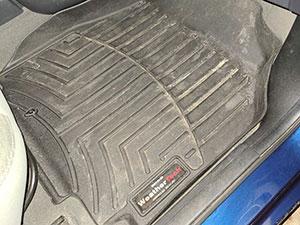 view of passenger side black floorliners in car