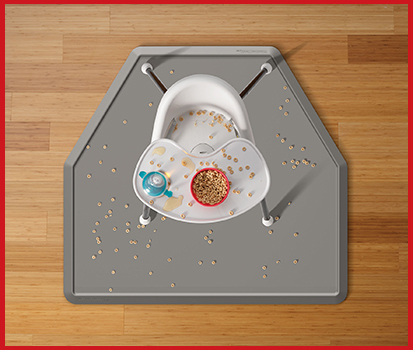 Photograph of an All-Purpose Mat under a high chair holding a mess of spilled food in a home.