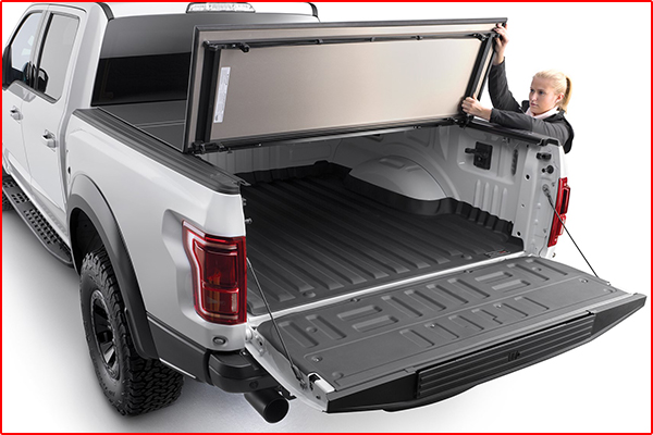 A woman folding up a hard tri-fold truck bed cover panel on a white pickup truck