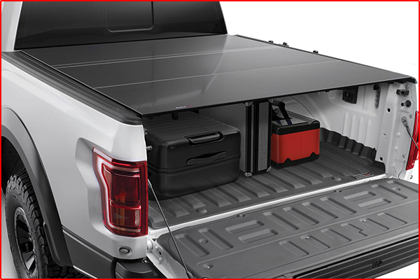 A hard tri-fold pickup truck bed cover installed on a white truck