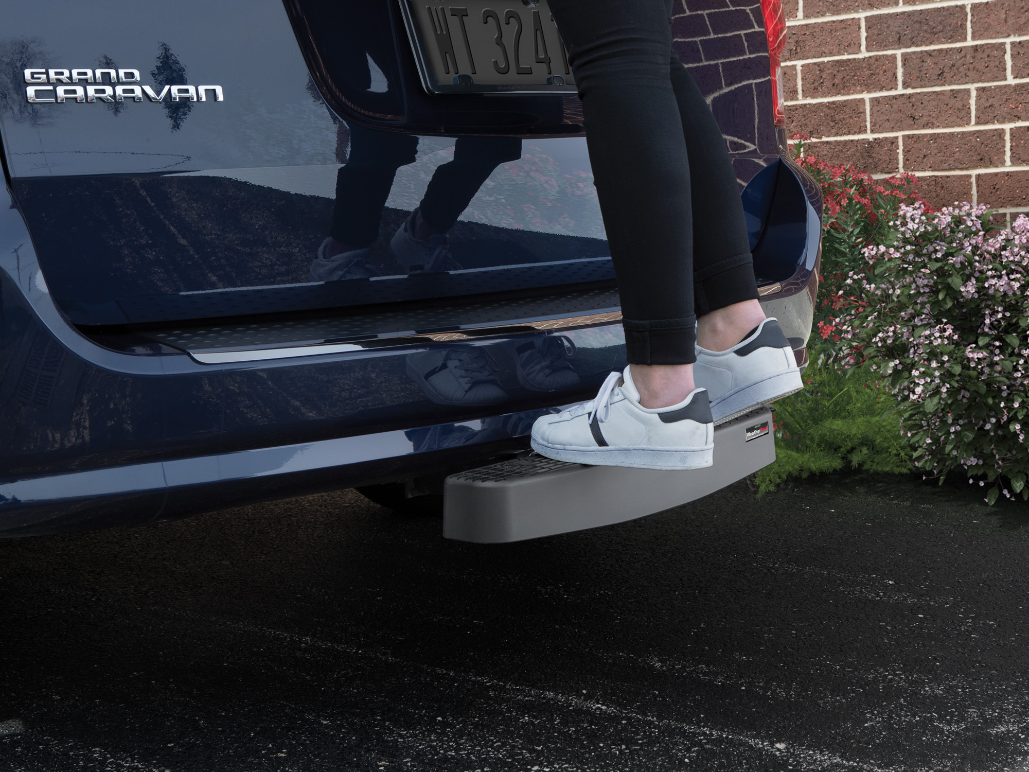 Woman standing on WeatherTech BumpStep XL rear bumper protector.