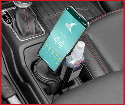 Photograph of a CupFone with Hand Sanitizer holder attached resting in a vehicle cup holder.