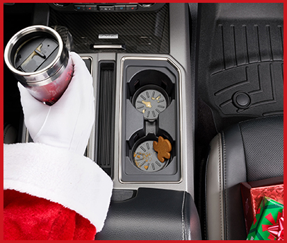 Photograph of Santa driving and holding a coffee thermos with the CarCoasters product inserted into the cup holders.