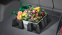 Spring plants and watering can secured in a vehicle with WeatherTech CargoTech.