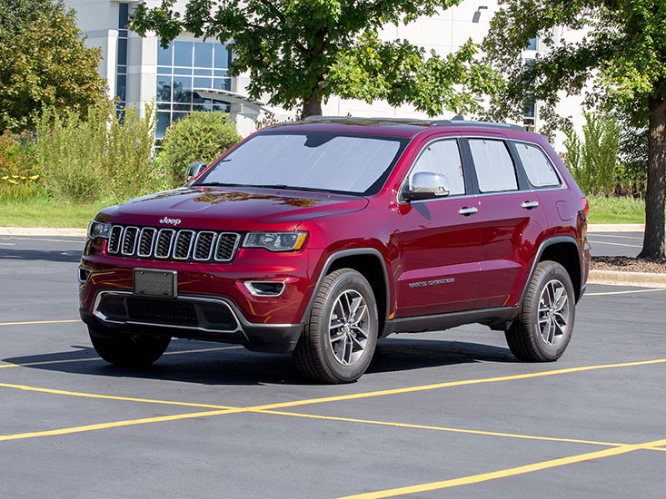 Red Jeep Grand Cherokee in sunny parking lot with WeatherTech SunShade in windows.