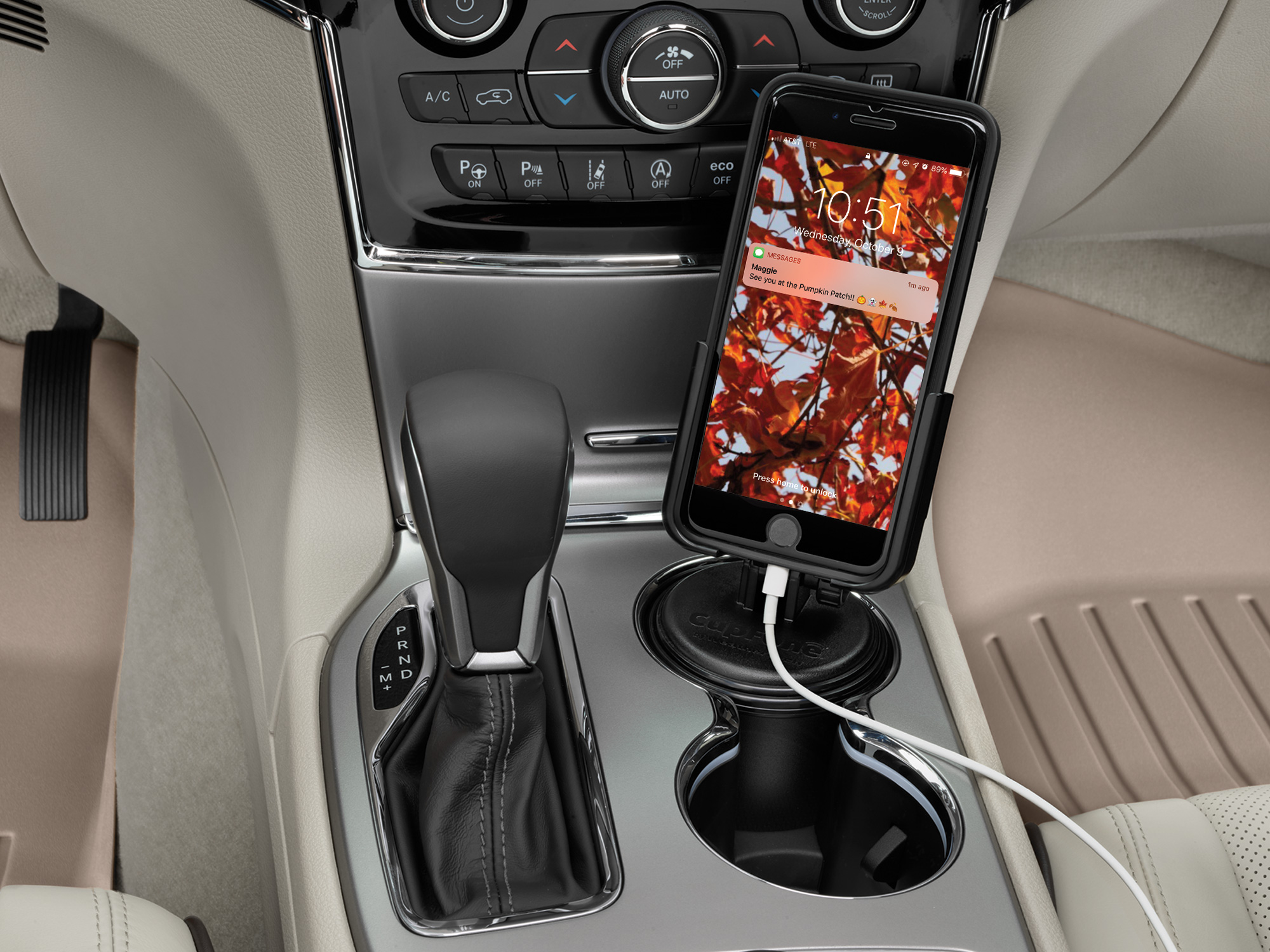 WeatherTech CupFone in the cup holder of a vehicle with fall imagery on the phone's screen.