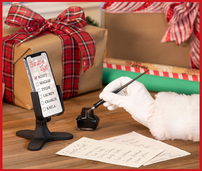 Photograph of Santa making a list with a phone resting in the DeskFone at his desk.