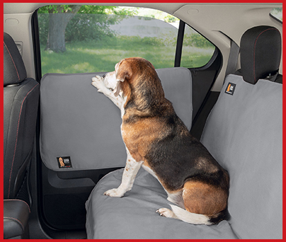 Photograph of a dog sitting in the backseat of a vehicle with his paw resting on a Door Protector that covers the rear door.