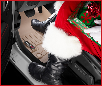 Photograph of Santa's boots driving a vehicle with FloorLiners installed.