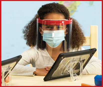 Photograph of a child at school with a tablet wearing a FaceShield Air.