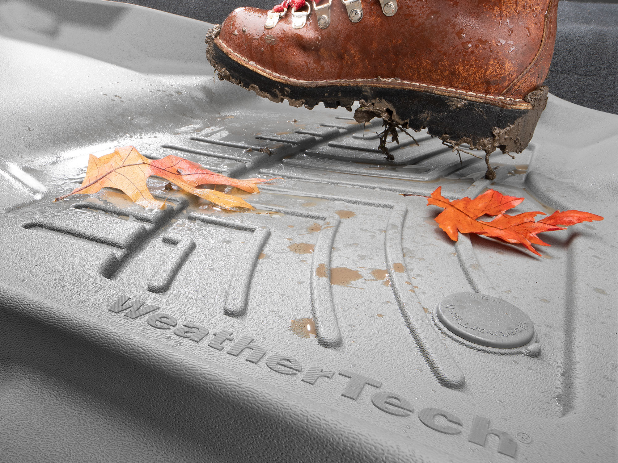 Grey WeatherTech FloorLiner HP covered in muddy water, autumn leaves and a muddy boot.