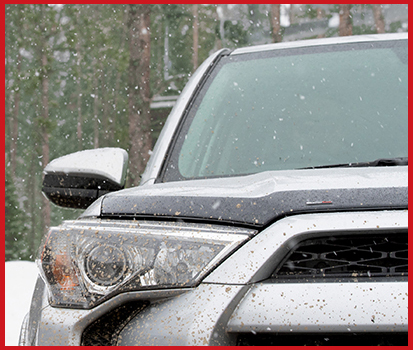 Image shown of the grill of a vehicle with a Hood Protector attached to the hood outside in the snow.