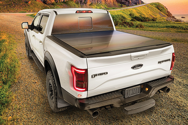 White pickup truck at dusk with hard truck bed cover installed.