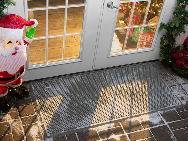WeatherTech OutdoorMat covered with snow outside a house in winter time.