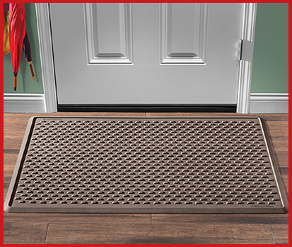 Photograph of an IndoorMat on the floor near a front door in a home.