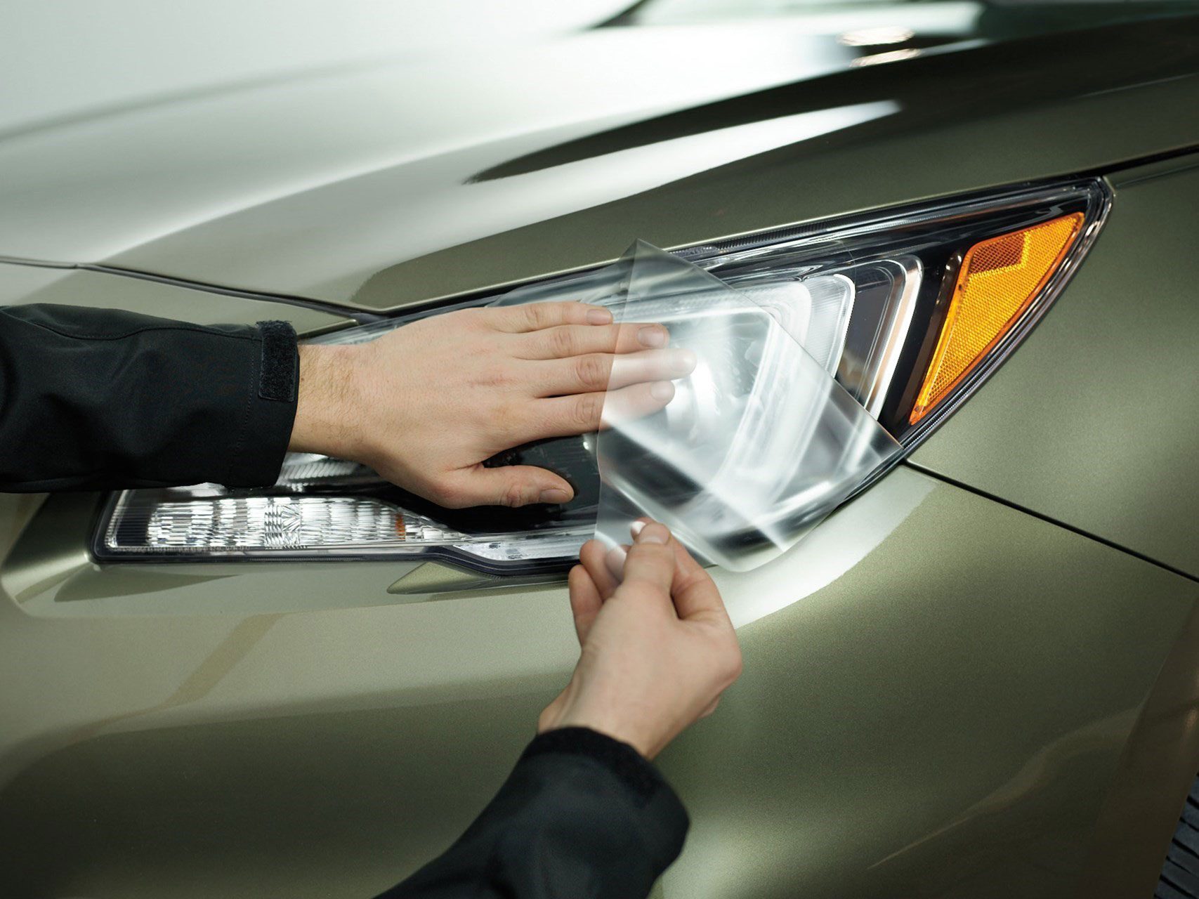 WeatherTech LampGard being installed onto the headlight of a car.