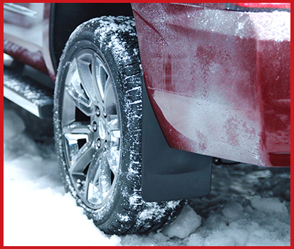 Image shown of a vehicle driving through snow with MudFlaps attached to the fender preventing slush and unwanted grime.