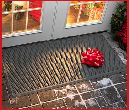 Photograph of our OutdoorMat with a bow on the ground outside of a backdoor.