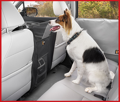 Photograph of an adorable dog sitting in the back seat calmy with a Pet Partition attached between the two front seats that prevents the dog from jumping on the center counsel.