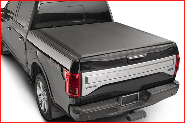 A roll up truck bed cover installed on a black truck.