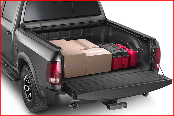 A truck bed cover rolled up exposing cargo in the bed of a black pickup truck