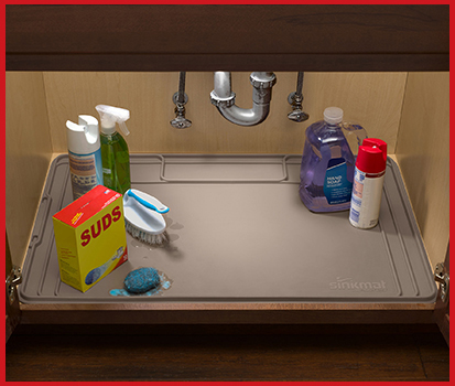 Photograph of a SinkMat under a sink with various cleaning supplies on it.