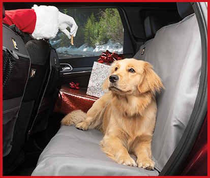 Photograph of a golden retriever sitting on Seat Protector in a vehicle with gifts behind her.