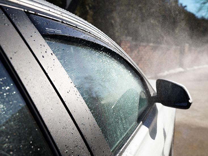WeatherTech Side Window Deflectors on silver sedan being washed.