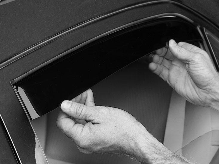 Rear driver side window deflector installation being finalized on dark sedan.