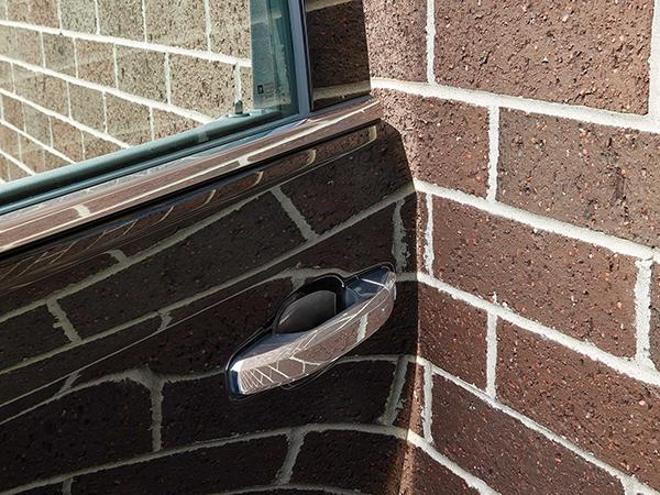 Car door rubbing against brick wall